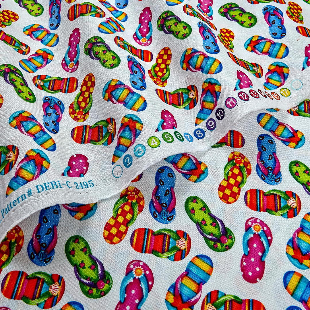 Flip flops tossed on white cotton fabric by Timeless Treasures fabrics C2495